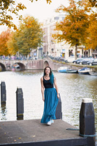 woman in blue skirt on dock of amsterdam canal