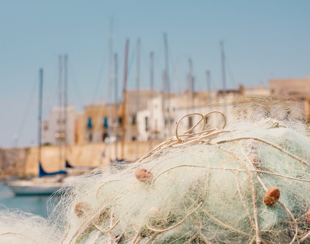 fishing nets with boats in the background in gallipoli italy under the summer sun